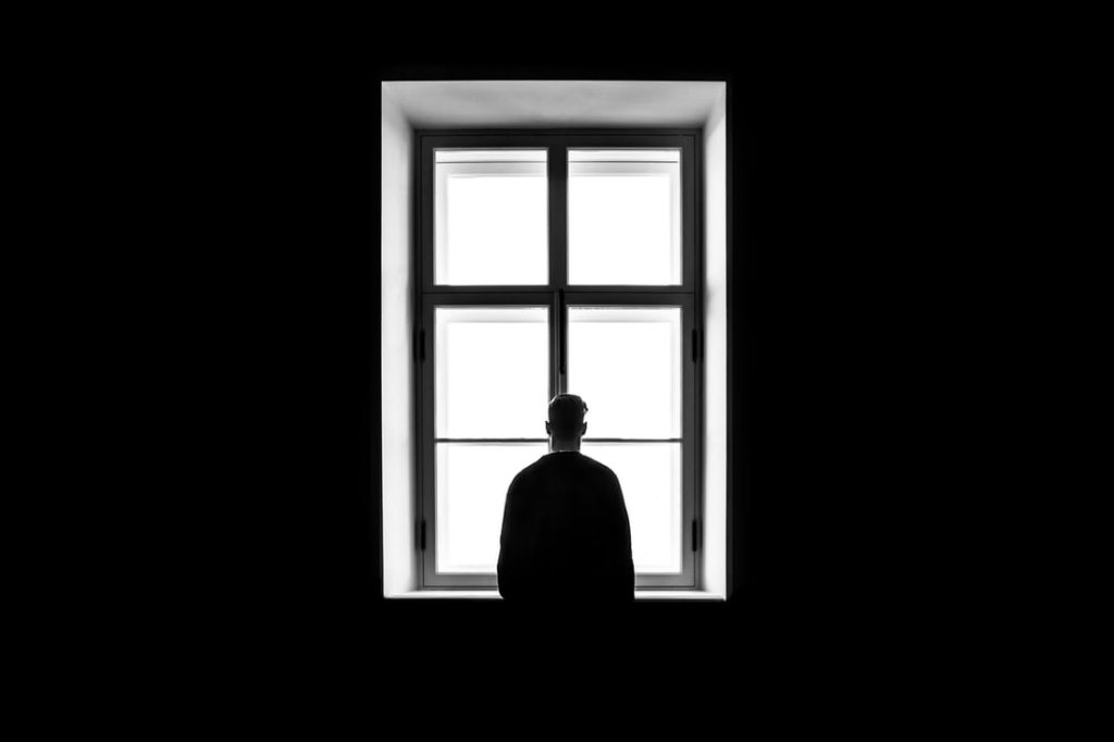 Depressed man alone at window