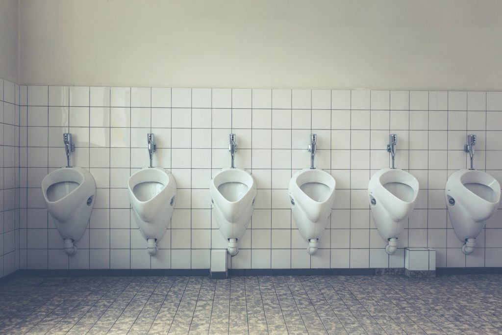 row of urinals - urinal etiquette guide image